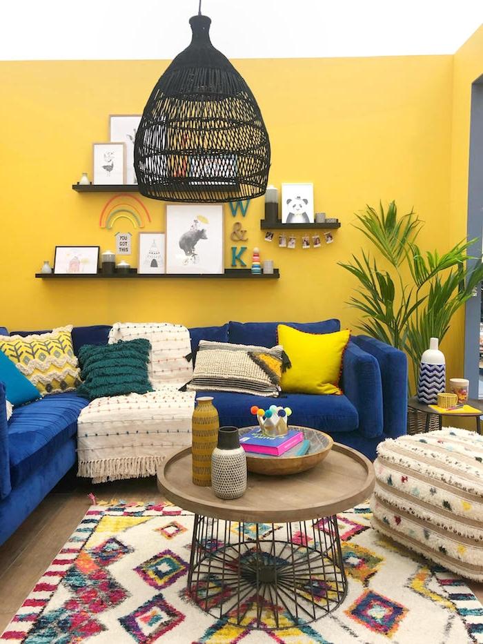 couleur mur salon jaune, canapé d angle bleu roi tapis coloré à figures géométriques, suspensions noires, parquet bois, coussins vert, jaune et blanc