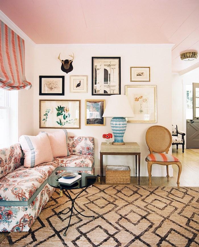 plafond repeint de rose, murs blancs décorés de cadres decoratifs d art, canapé d angle blanc décoré de détails colorés, tapis gris et noir