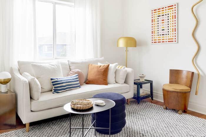 murs blancs, canapé blanc, tapis noir et blanc, table basse noire et tabouret bleu marine, murs blancs, mini fauteuil bois