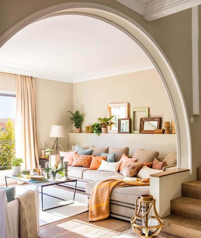 idée peinture salon couleur taupe clair avec canapé taupe décoré de coussins gris, saumon et bleus, table basse sur tapis et parquet bois