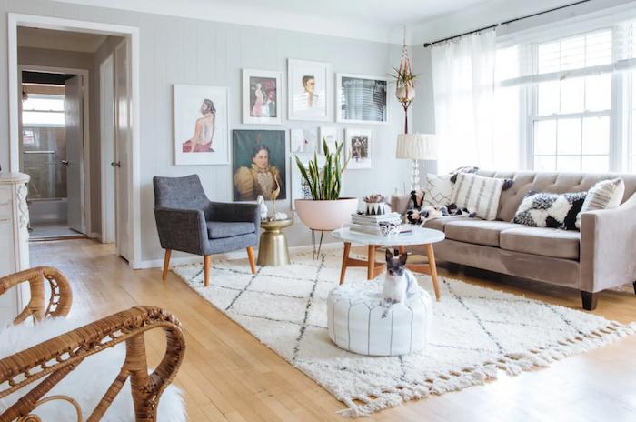 murs couleur blanc cassé, tapis shaggy scandinave, canapé gris velours, fauteuil gris foncé, parquet bois clair, mur de cadres, portraits d art