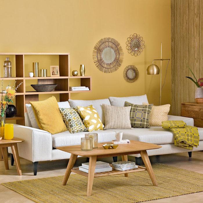 idée peinture salon jaune avec canapé blanc cassé surchargé de coussins jaune, gris et blanc, table basse bois, miroirs soleil