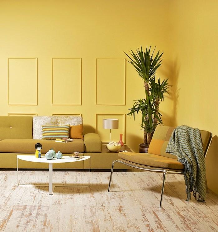 décoration peinture salon jaune avec canapé jaune de gris, table basse scandinave blanche sur parquet bois patiné