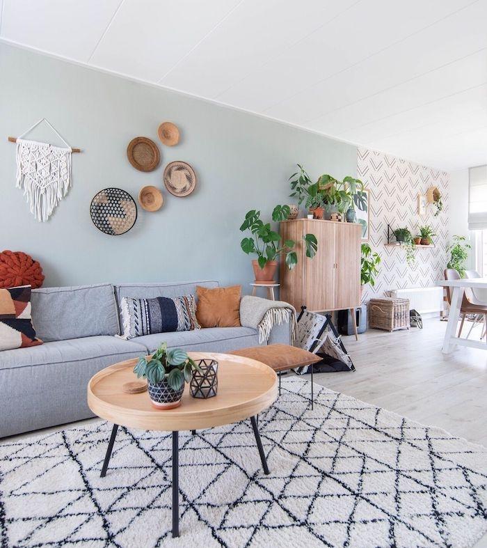 couleur vert de gris pour aménager un salon scandinave ouvert sur salle à manger, table basse bois et metal. canapé gris, macramé mural, parquet bois clair