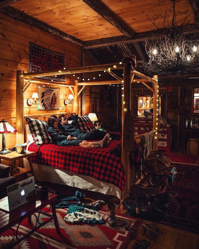 Couple déco chambre cocooning, deco rustique dans un chalet chic, lit avec guirlande lumineuse autour, déco de noel chalet