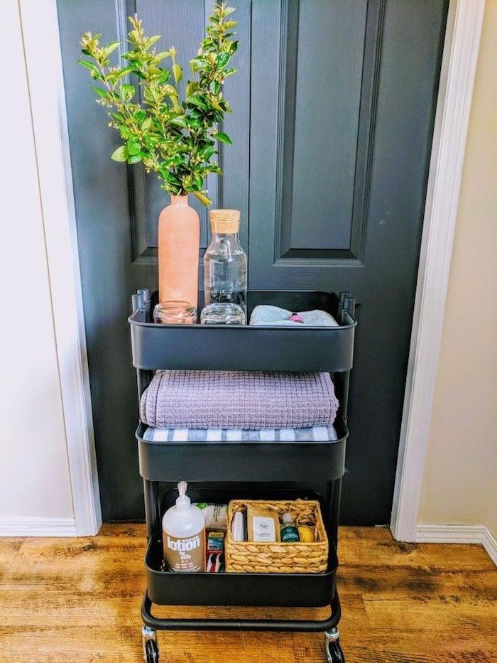 meuble desserte salle de bain astuce rangement, desserte noire pour ranger serviettes, panier avec produits de beauté et vase avec branches vertes