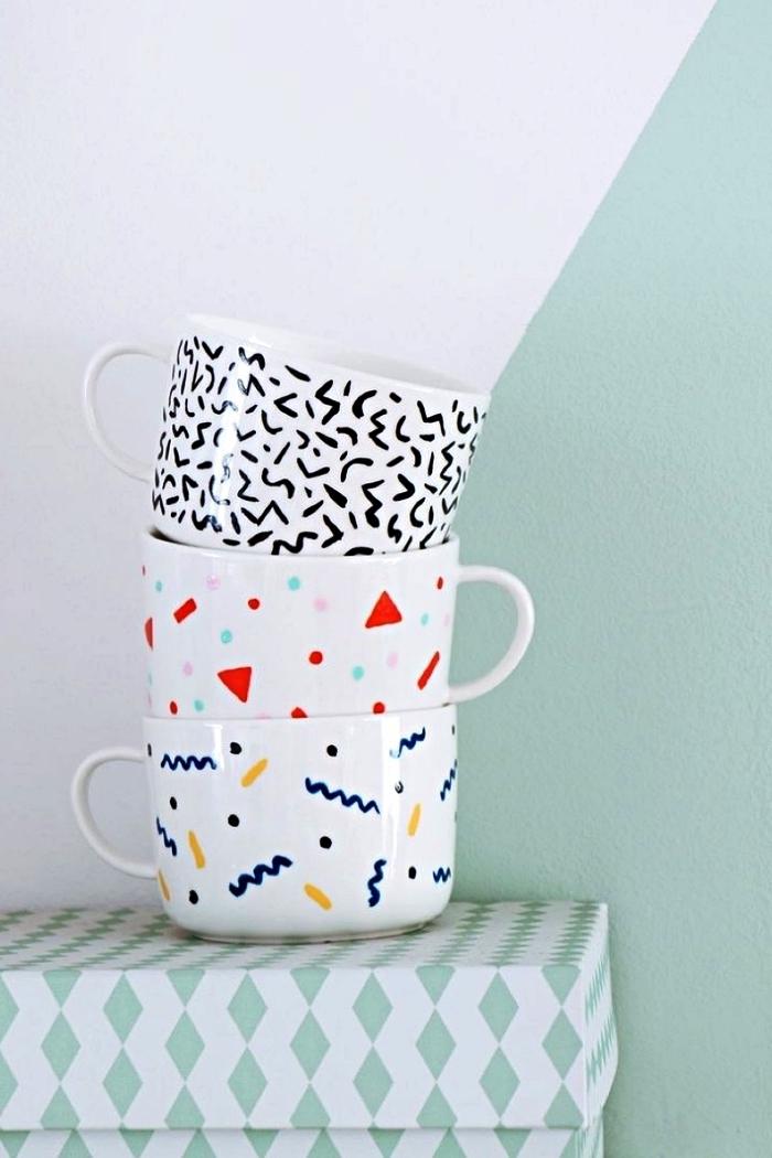 décorer des mugs blancs au feutre pour porcelaine, trois tasses à café à motifs graphiques modernes