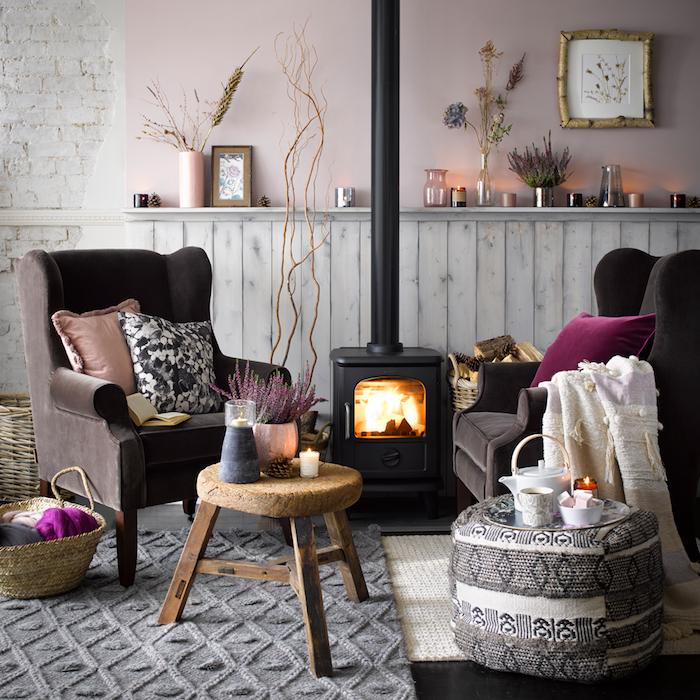 deco salon cocooning en rose clair avec fauteuils marron foncé, tapis gris tricot et pouf table noir et blanc, cheminée moderne