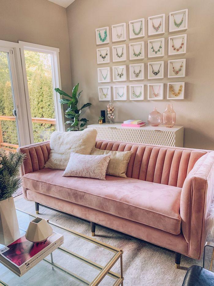murs couleur taupe clair pour amenager un salon feminine avec canapé rose poudré velours, tapis gris, accents vert et rose