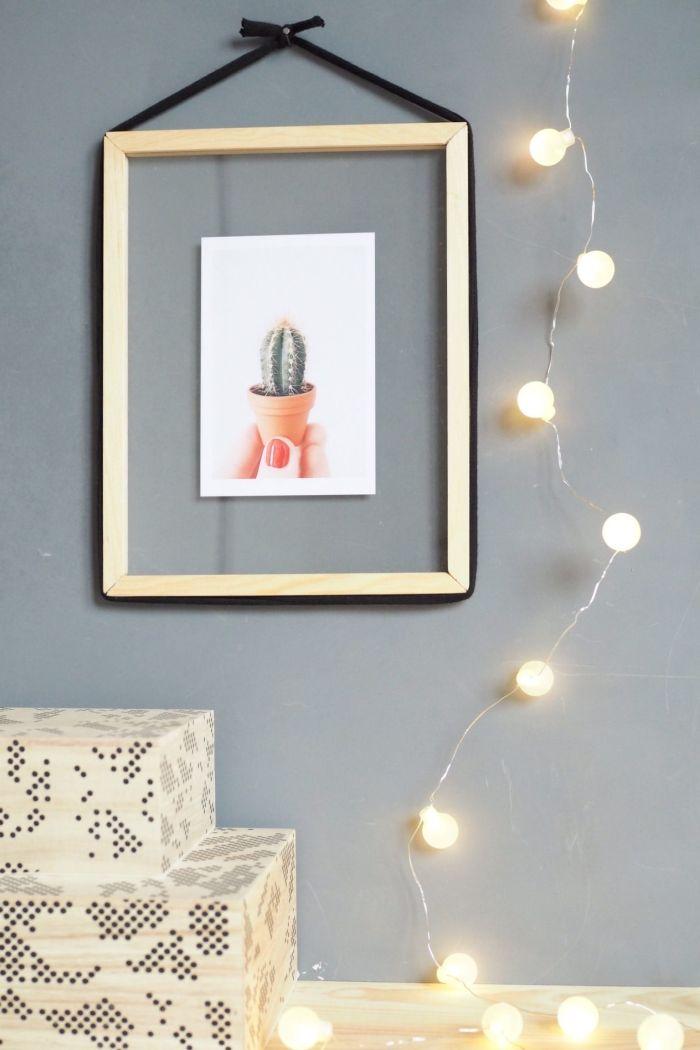 cadre mural flottant en acrylique avec encadrement bois suspendu au mur et mis en valeur par une guirlande lumineuse