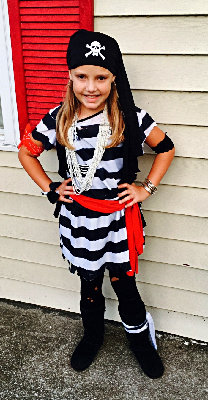petite fille déguisée en pirate portant une blouse rayée en, un foulard rouge autour la taille et un foulard à tête de mort, deguisement pirate enfant de dernière minute à faire soi-même