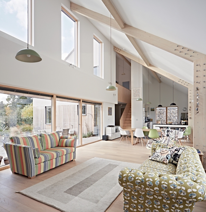 exemple d'amenagement salon avec plafond à une pente, idée déco salon ouvert en blanc et bois avec accents en vert