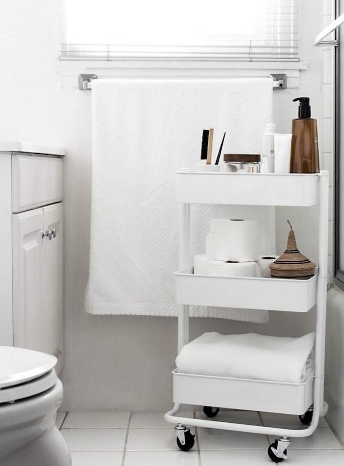 astuce rangement salle de bain avec desserte blanche pour ranger serviette, rouleaux de papier toilette et produits beauté