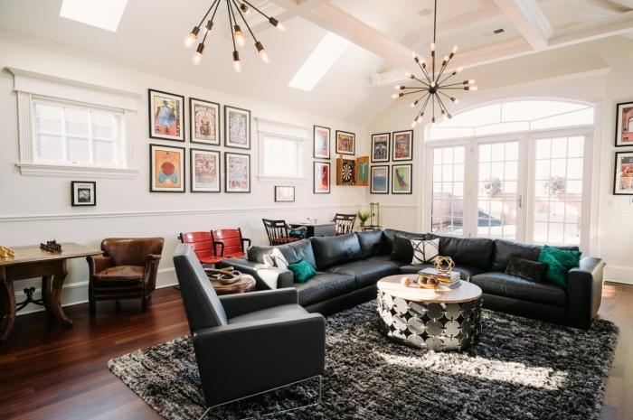 idée déco murale avec peintures à cadres noirs, deco salon moderne aux murs blancs avec canapé en cuir noir