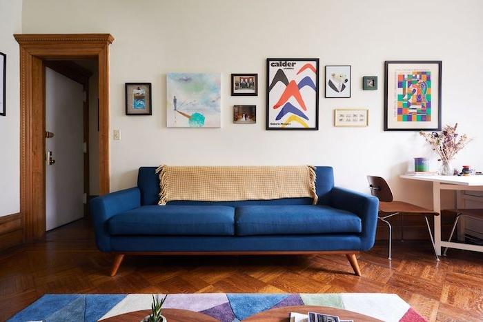quelle couleur de peinture pour plus de lumiere, murs couleur ecru, canapé bleu roi sur parquet bois foncé, tapis en tons pastel coloré