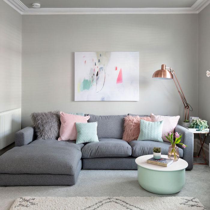 canapé d angle gris décoré de coussins en tons pastel, table basse couleur menthe, sol recouvert de moquet gris, murs gris, deco mural cadre peinture abstraite