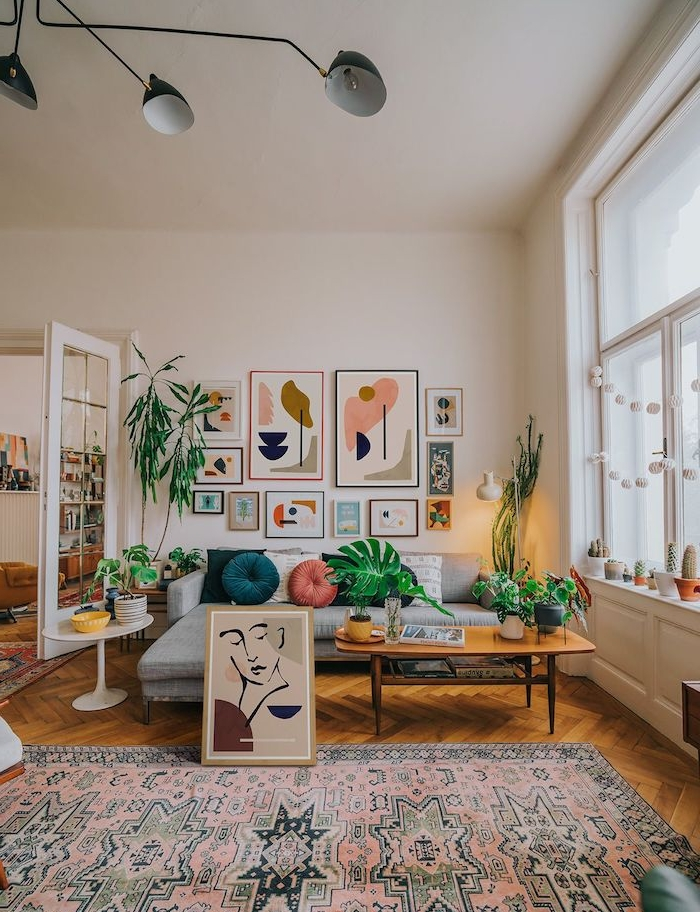 couleur blanc cassé pour les murs d un salon spacieux, canapé d angle gris, tapis oriental, table basse bois sur parquet bois clair, mur de cadres, deco mur salon artistique