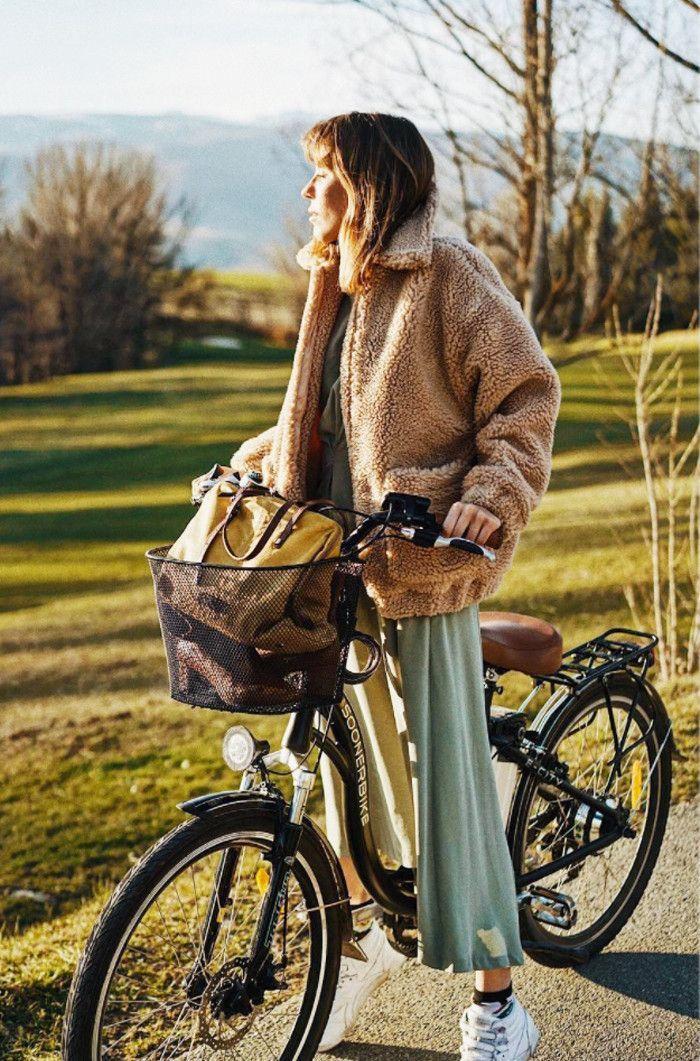 Bicyclette avec basket, femme en robe longue fluide et manteau fausse fourrure, tenue hiver femme moderne