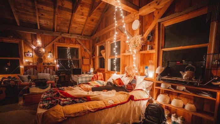 Murs bois avec guirlandes lumineuses, femme qui lit son livre sur le lit, interieur chalet, déco salon cocooning, deco rustique chalet