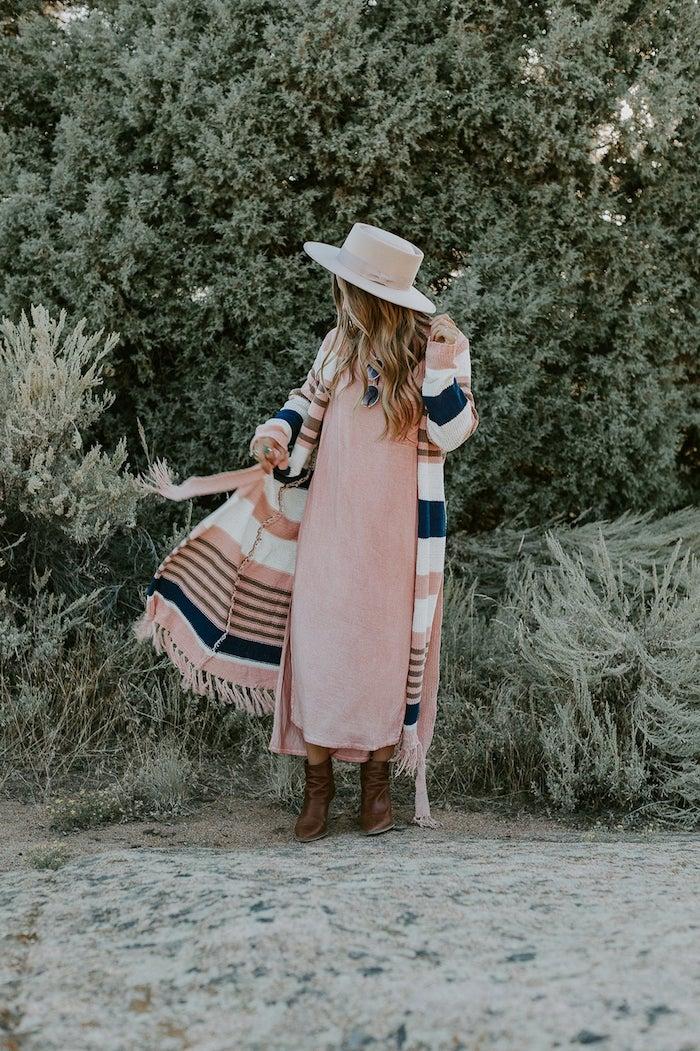 Femme habillée en robe rose pale et gilet longue à couleurs pastel, idée tenue bohème chic, chapeau avec grande périphérie