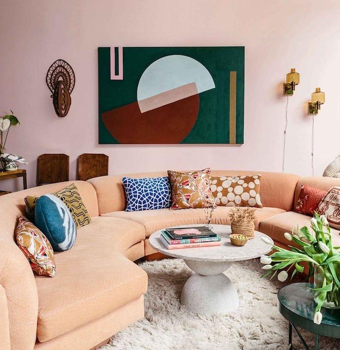 peinture interieur rose rose pastel pour les murs, canapé en u couleur saumon, coussins décoratifs colorés, tapis shaggy blanc, mur décoré de tableau art abstrait