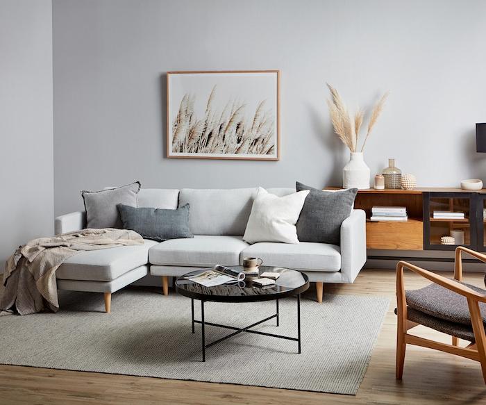 salon couleur gris perle avec canapé blan cassé tapis gris clair, table basse noire, tapis gris et parquet bois clair, mobilier de salon bois, deco scandinave