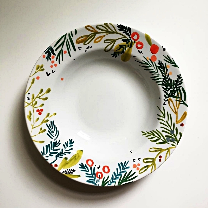 personnaliser une assiette blanche avec de la peinture céramique, peindre des motifs végétaux sur une assiette pour un design de noël