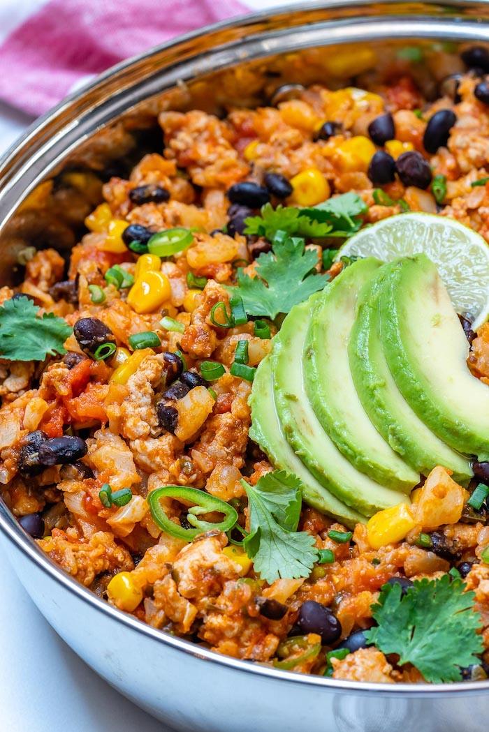 repas mexicain, casserole de riz de chou de fleur, viande hachée, haricots noirs, maïs et tranches d avocat