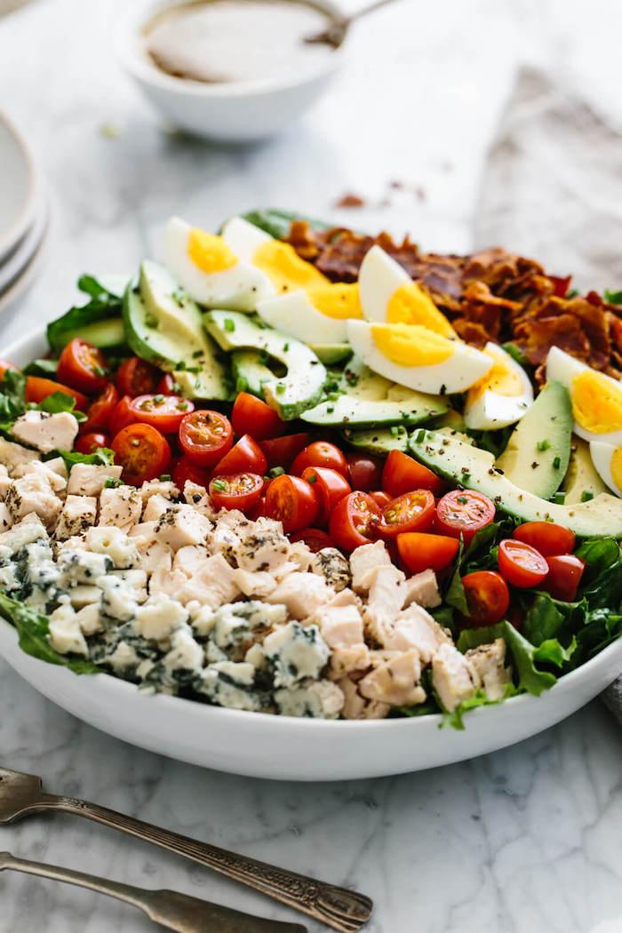 recette salade composée originale aux cubes de viande de poulet, salades vertes, tomates cerise, bacon, tranches d avocat et d oeuf dur