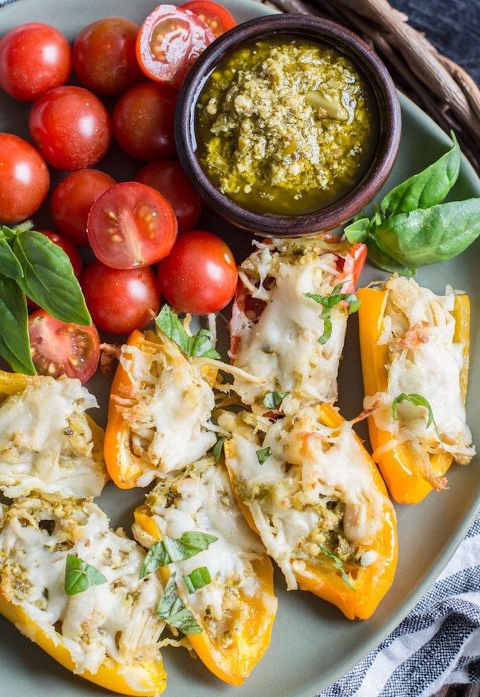 menu équilibré pour perdre du poids, poivrons jaunes farcis de poulet avec fromage rapé en top et sauce pesto