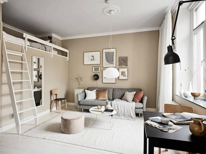 couleur taupe clair en peinture murale pour amenager un salon scandinave avec canapé gris, table basse blanche ronde, lit estrade