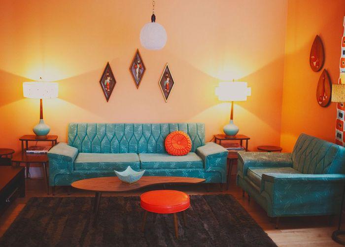 murs repeints de couleur orange interieur, canapé et fauteuil bleu, tapis marron foncé, coussin et tabouret orange, eclairage interieur original