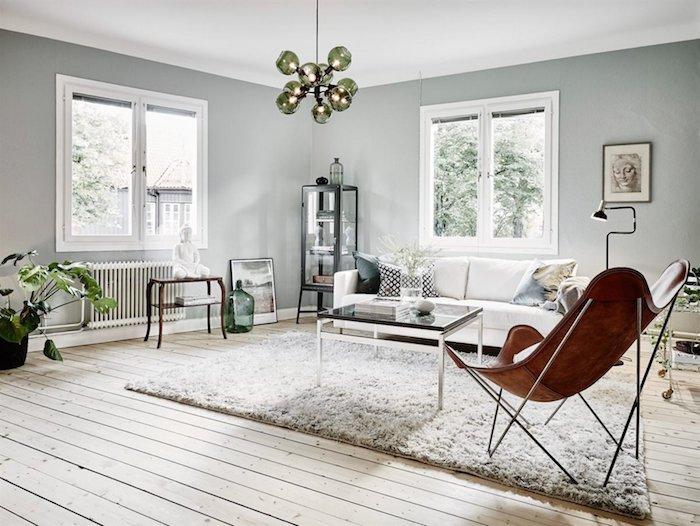deco salon gris style scandinave avec canapé blanc, fauteuil marron en cuir, suspension originale en couleur olive, ambiance zen créée avec statuette de bouddha