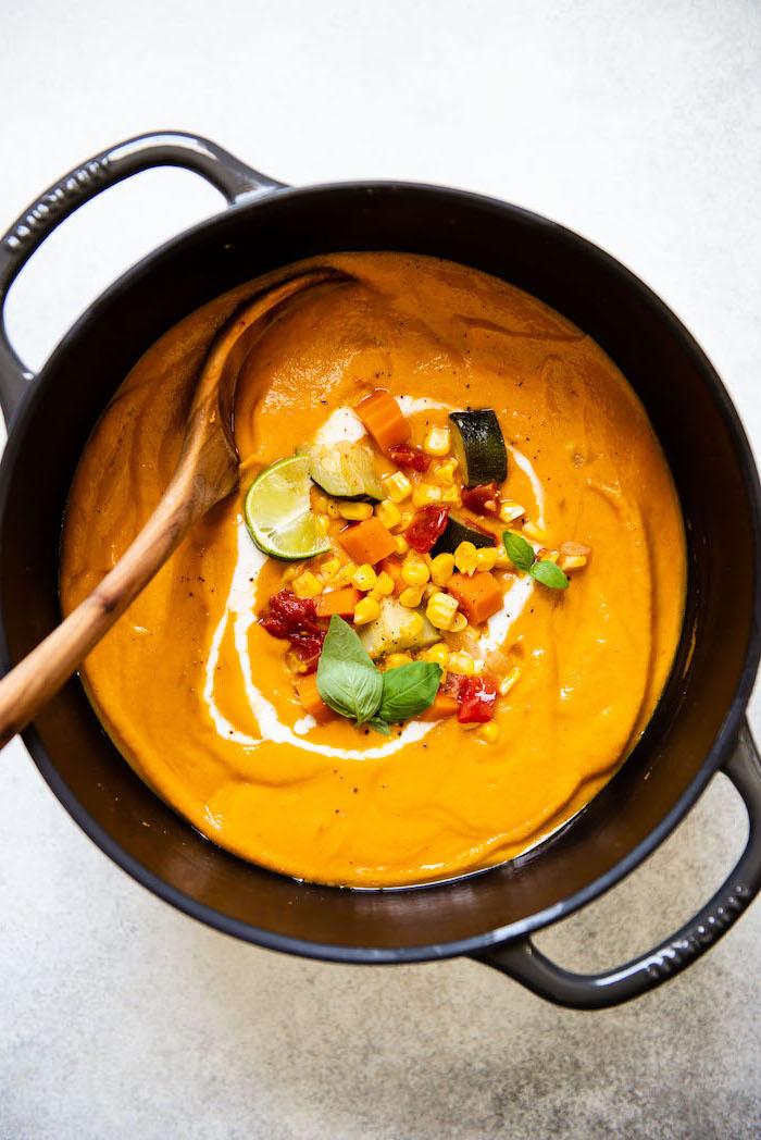 marmite remplie de soupe de légumes maison aux carottes, maïs, courgette, tomate, lait de coco et curry