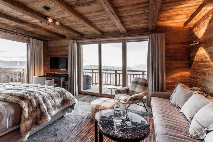 Chambre à coucher interieur chalet, déco chalet cosy chambre bois, confortable lit et coin de repos avec canapé, grande fenetre avec belle vue, balcon vue montagne