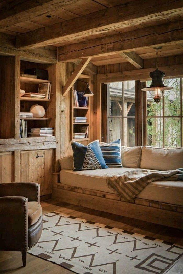 Canapé sous le fenêtre, tapis géométrique, petit chalet en bois, déco chalet montagne idée déco