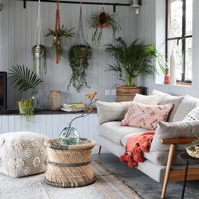 lambris gris dans un salon zen style deoc jungle avec canapé gris clair, table basse tressée, pots de fleurs suspendus