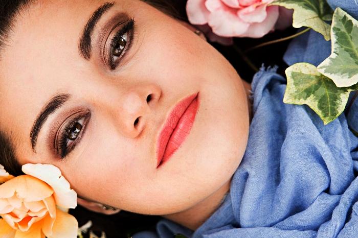 femme au visage de teint frais et unifié avec un regard souligné par fard à paupière dans les tons marron, les meilleurs produits en pharmacie pour maquiller la peau sensible