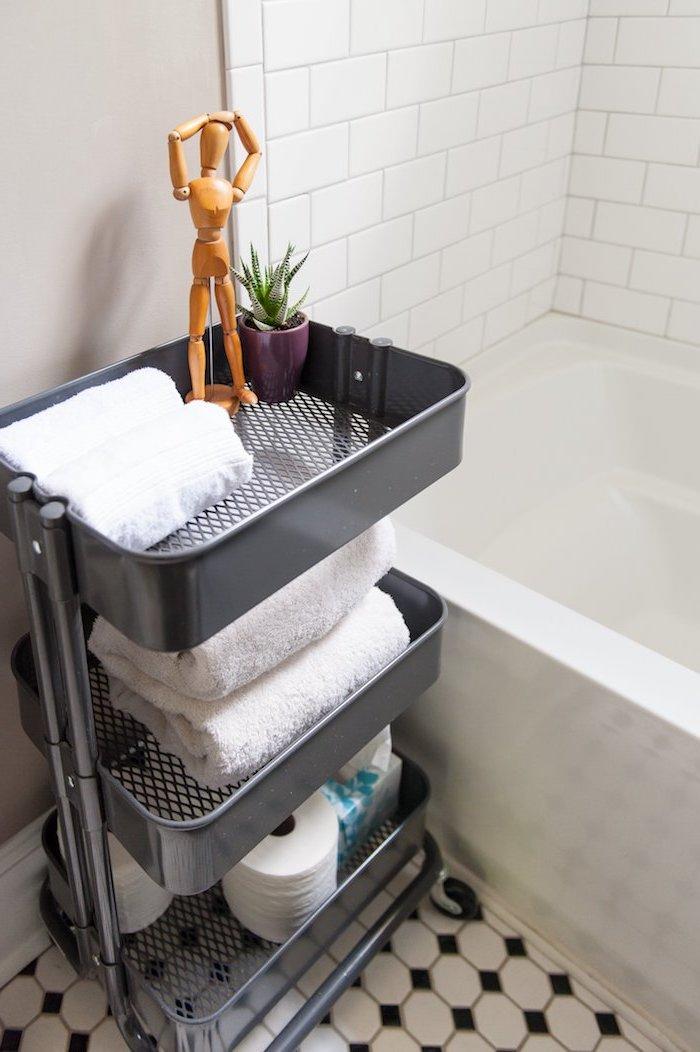 salle de bain noir et blanc avec carrelage damier, rangement raskog etagere noire pour organiser ses serviettes de toilette et autres produits salle de bain, baignoire blanche
