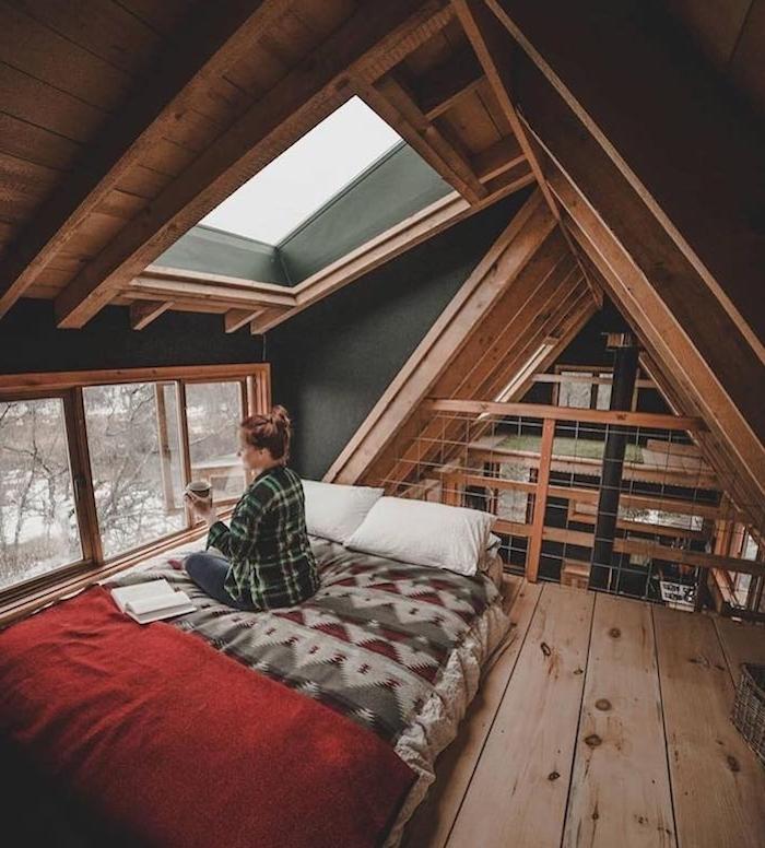 Femme assise sur son lit avec un livre et une tasse de café, deco chalet montagne, décoration scandinave en bois