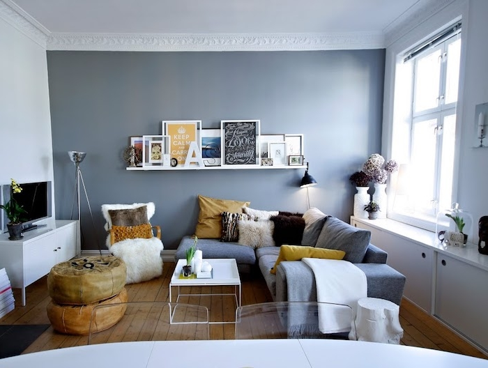 mur de fond couleur gris foncé dans une pìece habillée de blanc, canapé d angle gris décoré de coussins gris, jaune et marron, table base blanche sur parquet bois brut