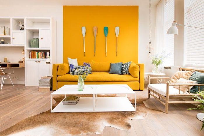 pan de mur couleur jaune vive et canapé jaune dans un salon blanc, deco murale originale en avirons, parquet bois clair et chaise de bois, tapis peau d animal