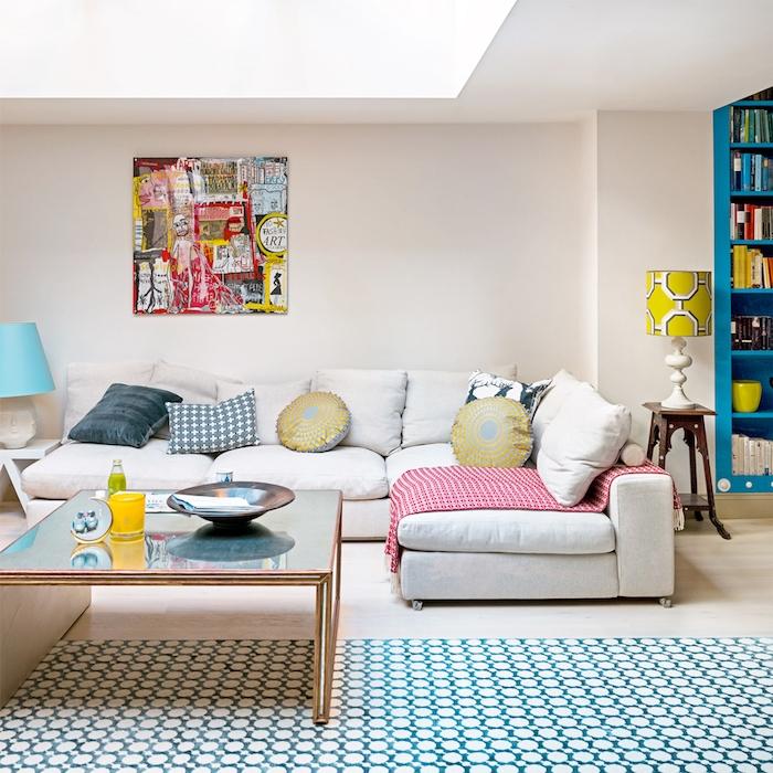murs couleur blanc cassé, deco murale pop art coloré, canapé blanc cassé, tapis bleu et blanc, table basse verre et laiton