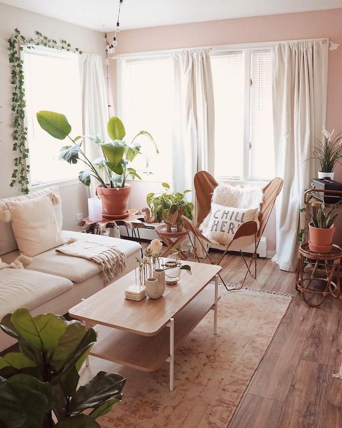deco junge salon cocooning en peinture rose clair, chaise marron, canapé blanc, table basse bois sur tapis marron clair, plantes vertes d interieur