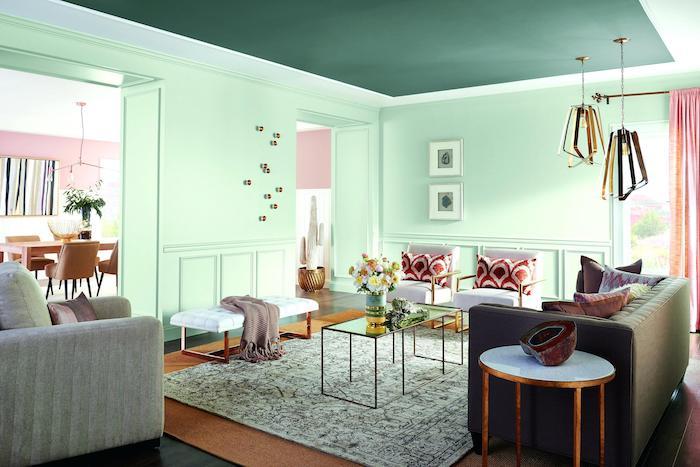 peinture couleur menthe dans un salon cocooning intimiste, canapé gris, table basse verre et metal, fauteuils blanc, coussins rouge et blanc, plafond vert foncé