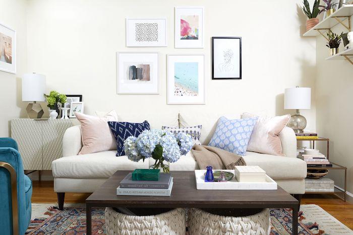 amenagement petit salon décoré avec canapé blanc décoré de coussins, table basse marron foncé, tapis coloré, bacs de rangement tressés