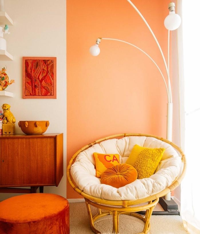pan de mur couleur saumon, mobilier de bois vintage et fauteuil oeuf cocooning avec coussin d assise blanc cassé et coussins decoratifs cosy