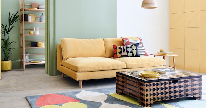 pan de mur jaune clair et pan de mur vert pistache, canapé jaune et tapis geometrique coloré, idee de salon pastel
