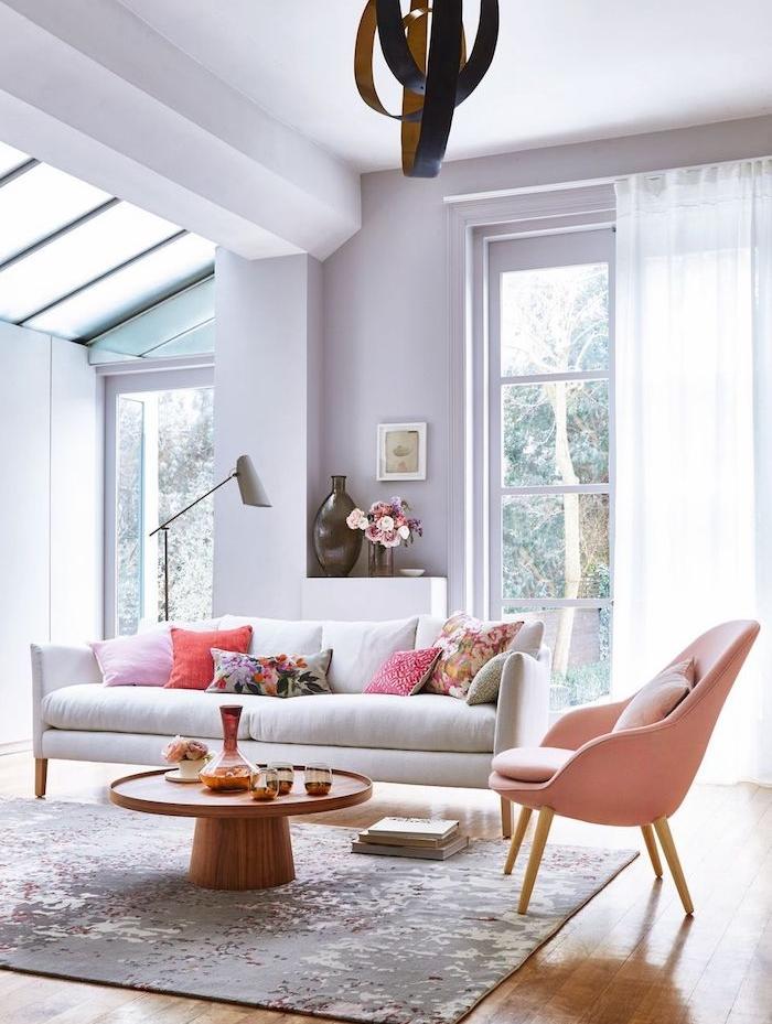 salon couleur mauve peinture lavande clair, canapé blanc, fauteuil rose, tapis gris sur sol décoré de parquet bois clair, suspension originale