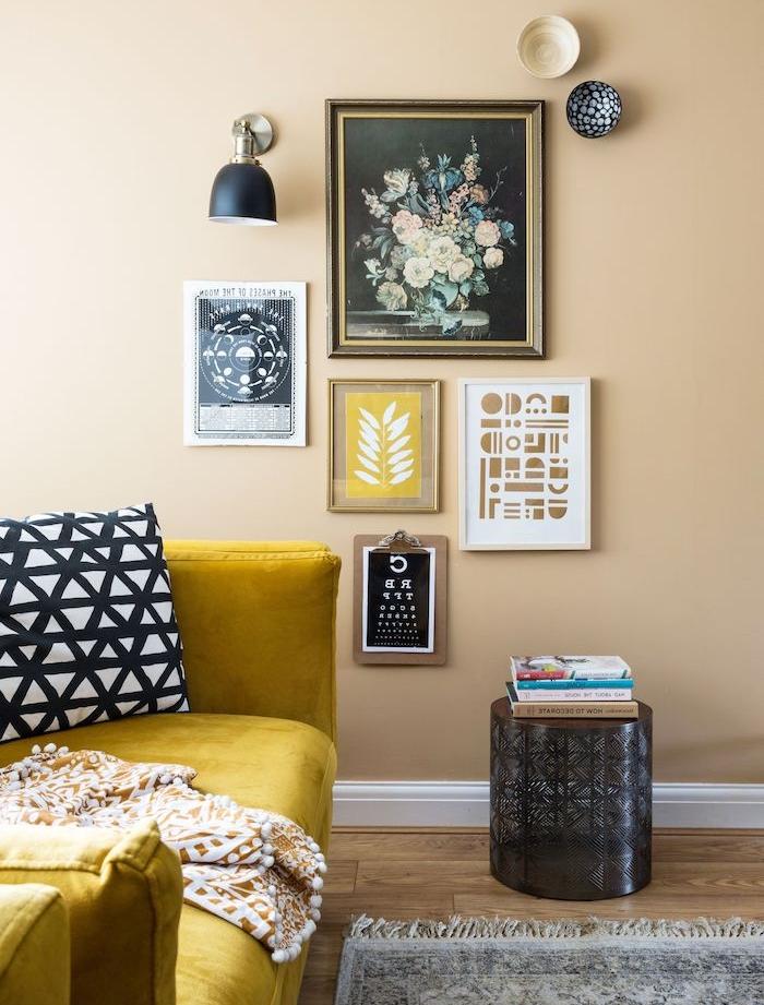 mur couleur taupe décoré de tableaux d art contemporain, canapé jaune, tapis gris sur son en parquet bois, idée peinture mur salon